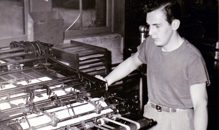 Leon Beaudoin standing by a flexographic press